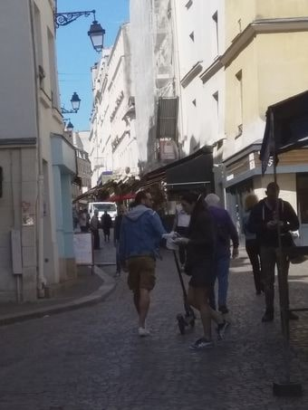 dans l'étroite rue Mouffetard, les gens font leurs courses dans les petits commerces de qualité (et pour portefeuilles bien garnis) comme si de rien n'était